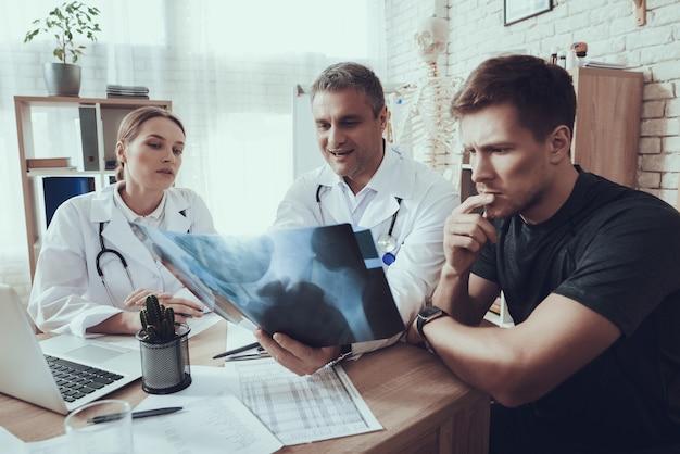 의사는 운동 선수에게 엑스레이를 보여주고 있습니다.