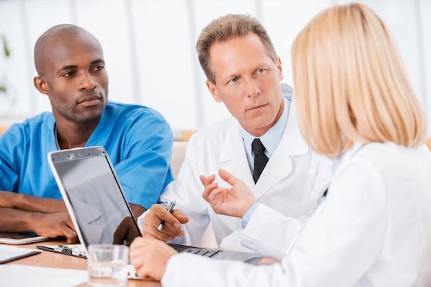 회의에서 의사입니다. 여자가 컴퓨터를 사용하고 몸짓을 하는 동안 3명의 자신감 있는 의사