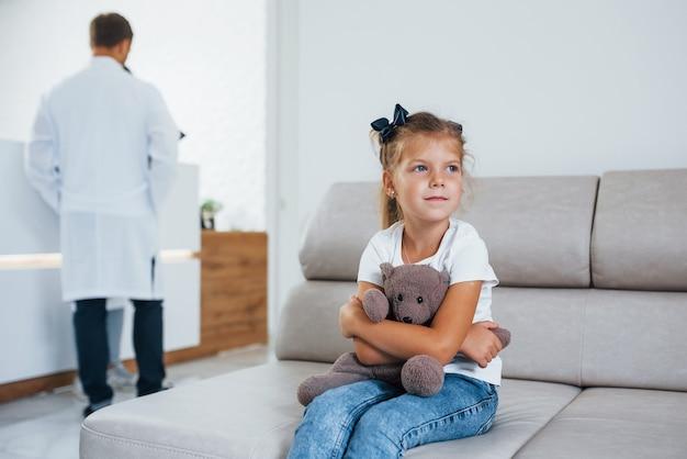 Врачи позади. милая маленькая девочка с плюшевым мишкой в руках сидит в зале ожидания больницы.
