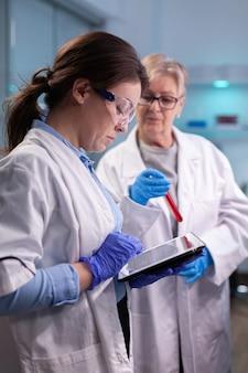 Medici chimici ricercatori in camice bianco che analizzano la provetta per analisi del sangue in un laboratorio attrezzato