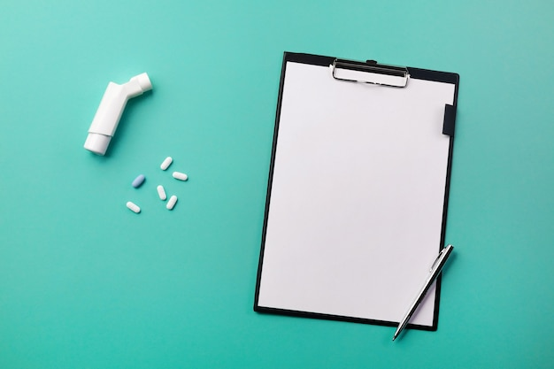 Doctors desk with tablet, pen, inhaler and pills. top view with place for your text.