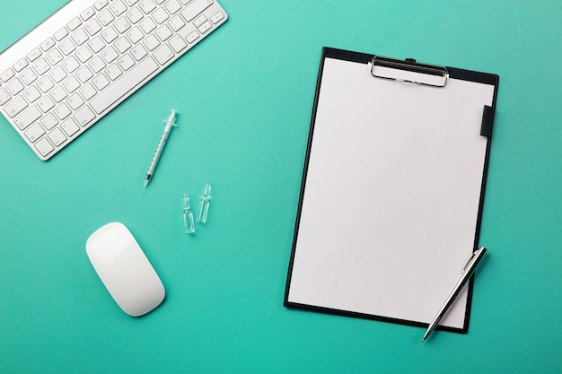 Doctors desk with tablet, pen, keyboard, syringe and ampoules