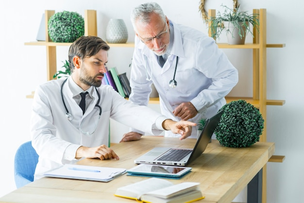 Doctors discussing data on laptop
