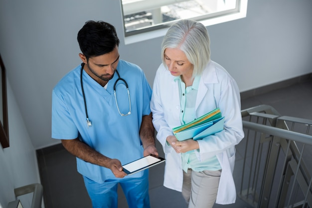 Doctors discussing over digital tablet while walking on stairs