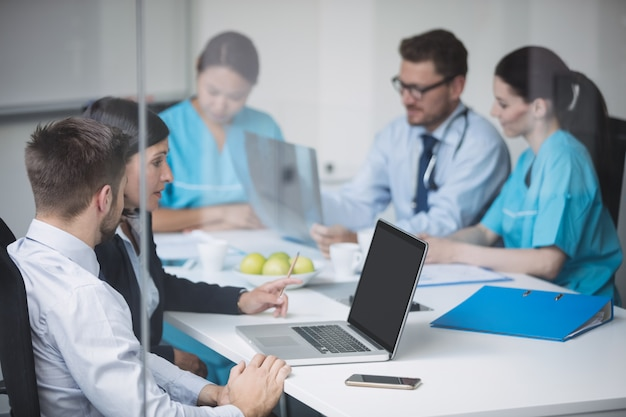 Doctors discussing over laptop in meeting