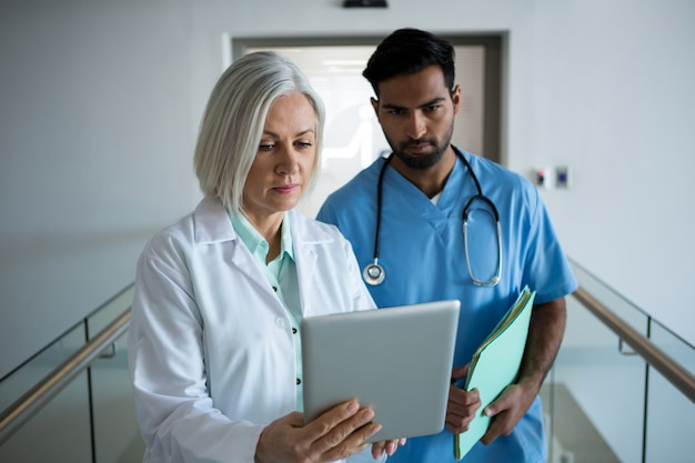 복도에서 디지털 태블릿을 통해 논의하는 의사