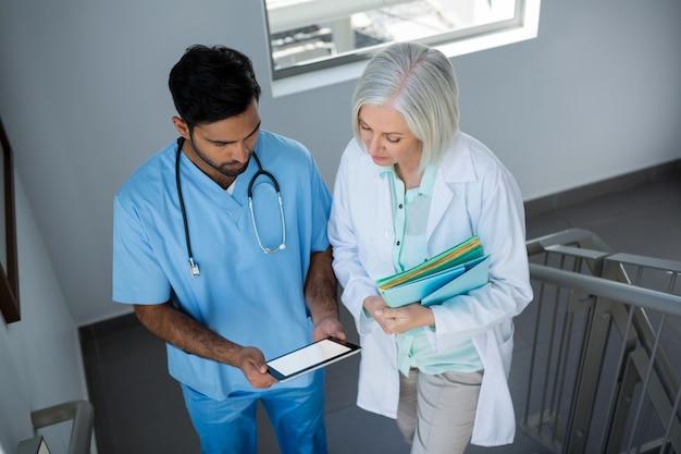 계단을 걷고있는 동안 디지털 태블릿을 통해 논의하는 의사