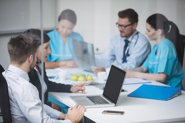 会議でラップトップを介して議論する医師