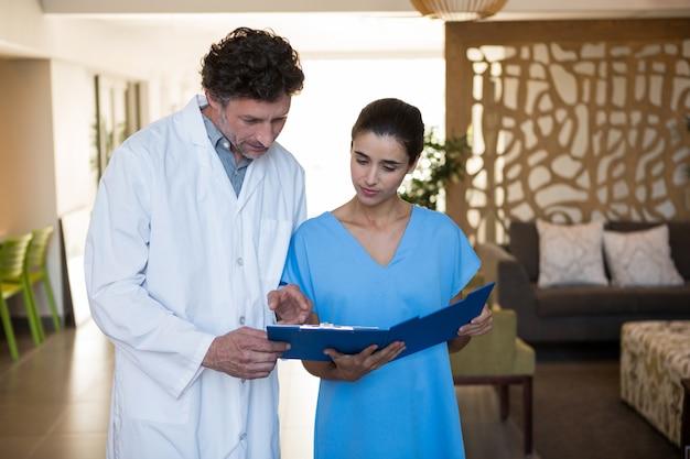 ファイルクリップボードの医療レポートを議論する医師