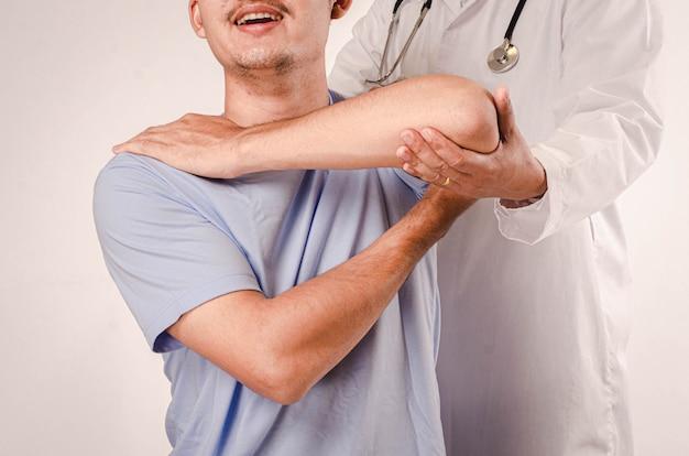 医師は若い男性の理学療法を行い、肩の問題のある患者にアドバイスします。