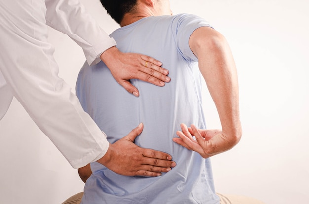 Doctors doing physical therapy for young men and advise patient with back-waist problems.