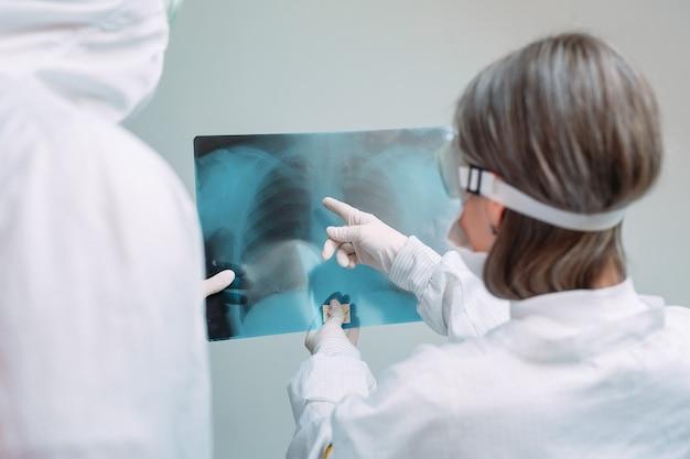 Врачи исследуют рентген на пневмонию пациента в клинике