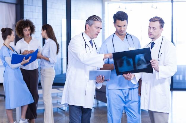 医師がレントゲンを検査し、病院で話し合いをしている