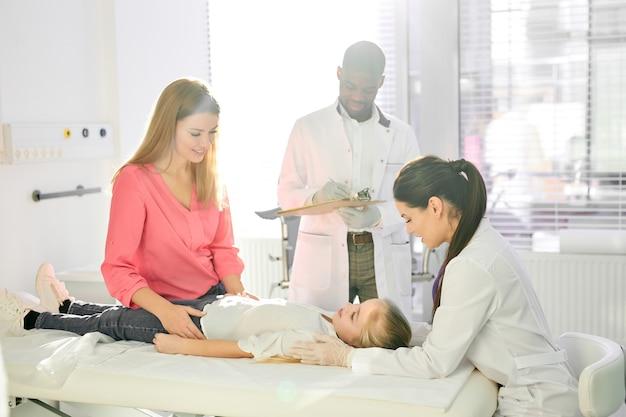 少女患者の健康状態を調べる医師、病院のベッドに横たわっている白人の十代の少女を治療するスーツを着た多様なアフリカ人と白人の医師、支えとなる母親が彼女の近くに座っています