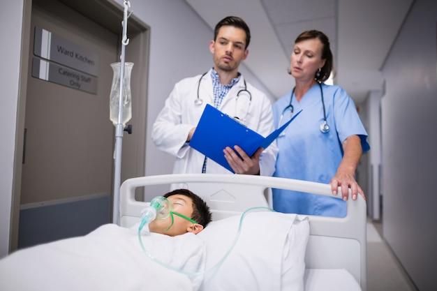 Doctors examining patient in corridor