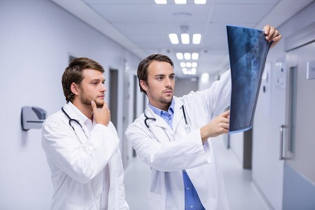 廊下でx線を調べる医師