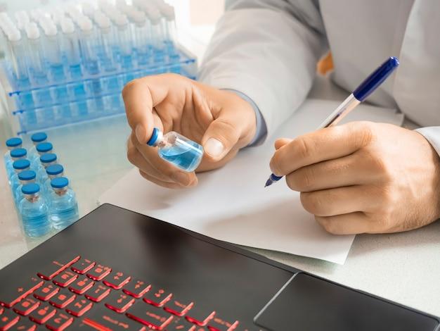 의사가 연구 저널에 항목을 작성하는 현대 백신이 있는 시험관을 들고 있는 의사