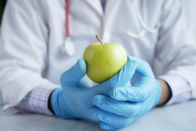 Врачи рука зеленого яблока, пока сидят