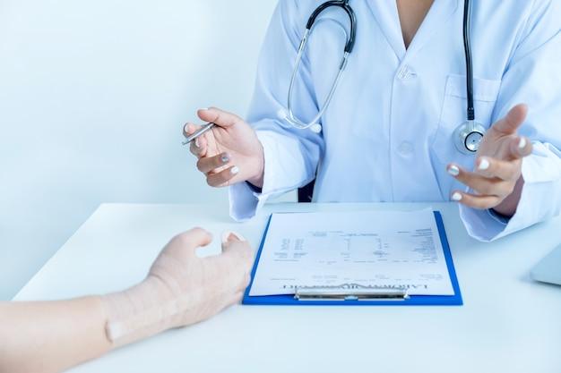 医師はペンを持って健康診断の結果を報告し、腕の事故の患者に投薬を勧めます。