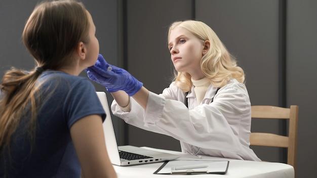의사들은 이동식 실험실에서 성인에게 코비드를 위한 비강 면봉을 가져가는 파란색 보호 의료 장갑을 손에 넣습니다.