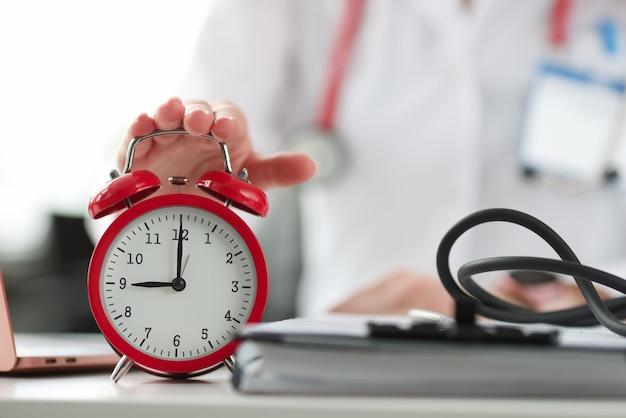 医師の手がオフィスのクローズアップで赤い目覚まし時計をオンにします。ポリクリニックコンセプトの営業時間