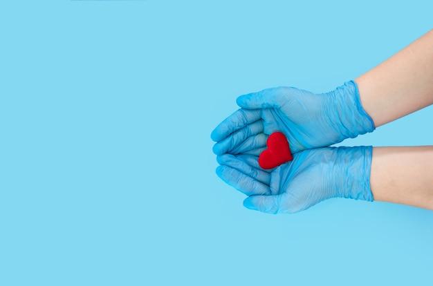 파란색 장갑에 의사 손을 잡고 파란색 표면 복사 공간에 마음을