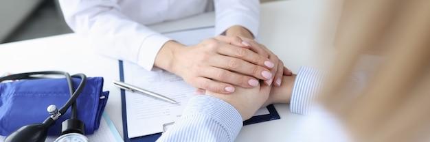 의사의 손은 환자의 팔에 돌이킬 수없는 건강 효과 개념에 동정적으로 누워 있습니다.