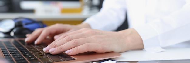 医師はラップトップキーボードのリモート医療支援の概念を実践
