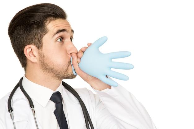 医者も楽しいです!白で隔離の医療用手袋を吹いて楽しんでいる男性医師のスタジオショット