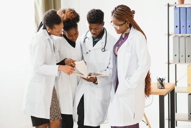 Врачи разговаривают, глядя на документы, смешанные расы, хирурги и врачи