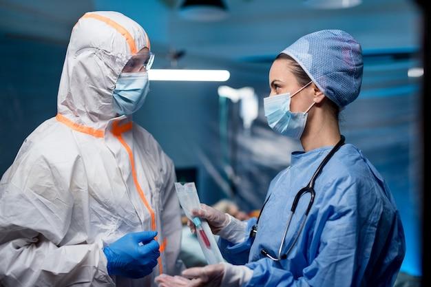 サンプルを保持し、病院で話している医師、コロナウイルスの概念。