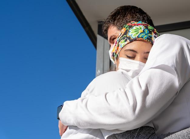 お互いを抱き締めるマスクの医者