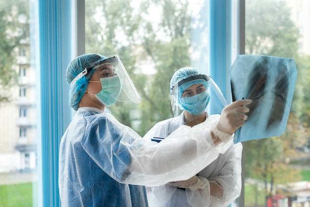 コロナウイルスのパンデミック時に防護服を着た医師が肺炎の治療について話し合う