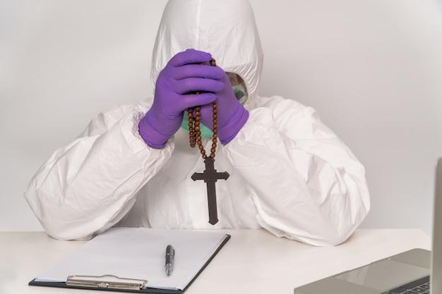 防護服とマスクを着た医師が十字架を持っており、感染症の治療と予防の希望を願っています
