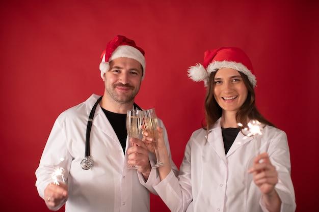 샴페인 잔으로 응원하고 폭죽을 들고 산타 클로스 모자에있는 의사