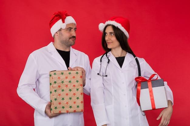 クリスマスのギフトボックスを保持しているサンタクロースの帽子の医師