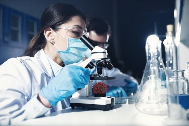 研究室の医師は顕微鏡下でサンプルを分析します。薬物治療の概念