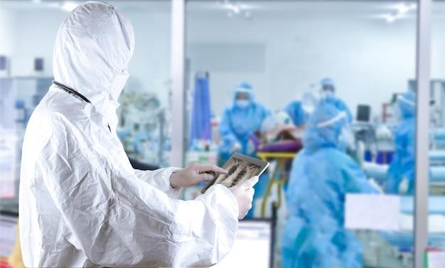 방호복을 입고 태블릿을 들고 있는 마스크를 쓴 의사들이 감염된 코로나 바이러스를 검사하고 있다 프리미엄 사진