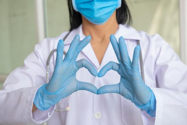 의사, 감염자, 연구 및 covid 19 concept. 의료 마스크와 라텍스 장갑에 손을 가진 여자는 심장의 상징을 보여줍니다. 심장을위한 닥터. 췌장에 대한 사랑. 의료 전문가