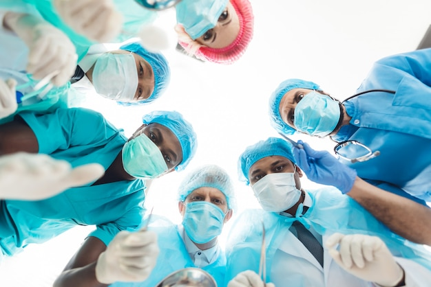Doctors look at patient who is lying on the operating table.