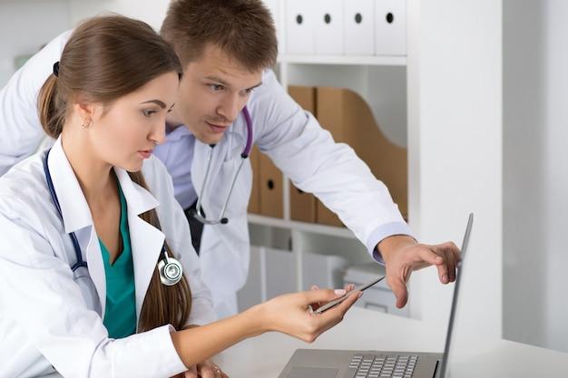 ノートパソコンのモニターを見て医師