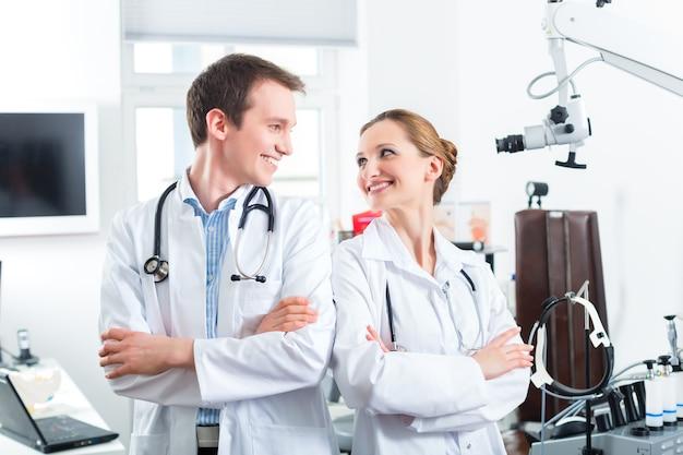 Врачи - мужчины и женщины, стоя со стетоскопом в клинике или кабинете врачей