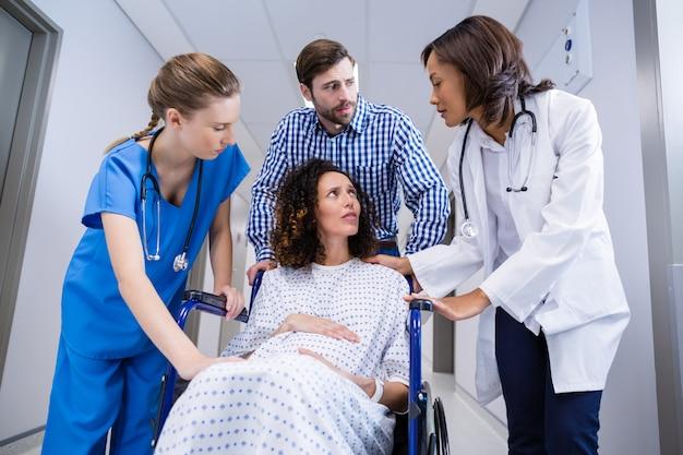 Doctors and man comforting pregnant woman in corridor