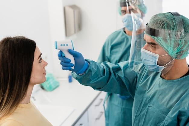コロナウイルスのパンデミック時に若い患者の発熱を測定する医師