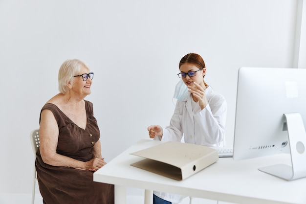 Doctors in the medical office talking to an elderly woman health care