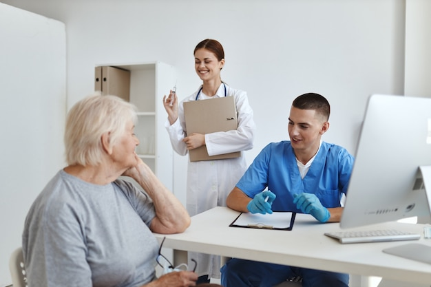 Врачи медсестра осматривают пожилую женщину пациента больницы здравоохранения