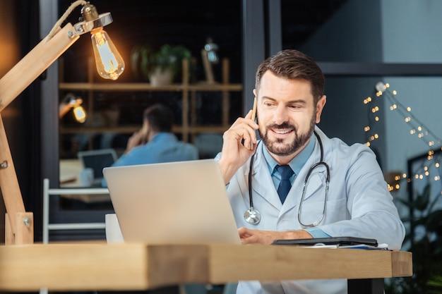 医院。ノートパソコンの画面の前に座って、彼のオフィスで働いている間電話で話している前向きな素敵な喜んでいる男