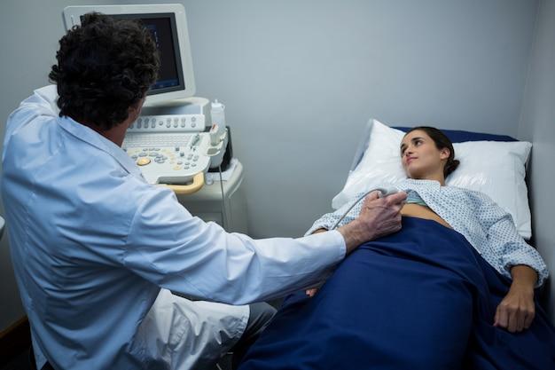 환자의 위장에 도플러 초음파를 수행하는 의사
