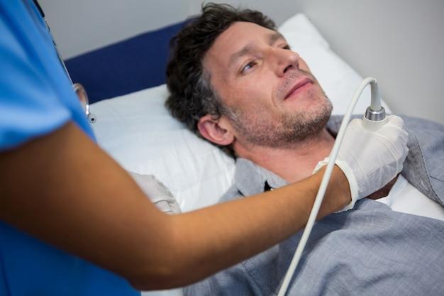 환자에 대한 도플러 초음파 검사를 수행하는 의사