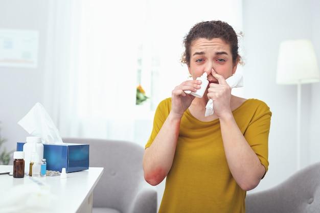 Рецепт врачей. молодая женщина, находящаяся в отпуске по болезни, старательно использует назальные капли, прописанные врачом, при лечении аллергии